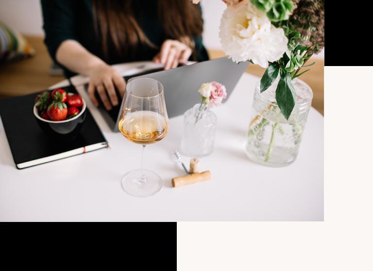 Ragazza che scrive computer con calice di vino e fiori