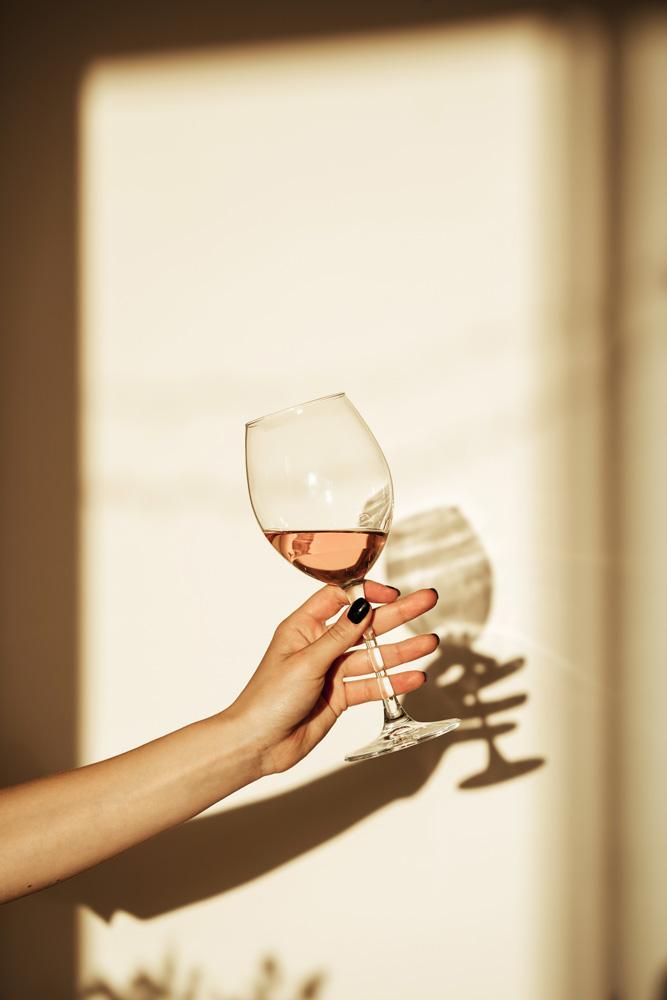 Mano di donna con bicchiere di vino in controluce
