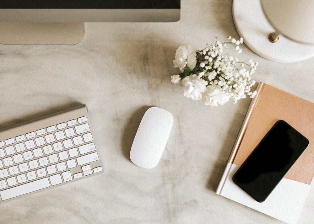 scrivania con tastiera computer, telefono, fiori