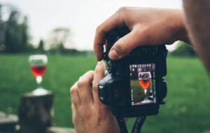 ragazzo con macchina fotografica che fotografa un bicchiere di vino