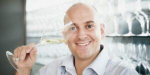 Ragazzo con bicchiere di vino bianco in mano