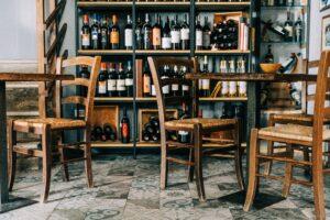 Bottiglie di vino in un'enoteca e tavolini di legno