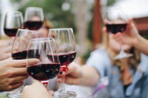 Persone che brindano con bicchieri di vino rosso
