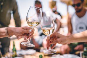 Due persone che brindano con vino bianco