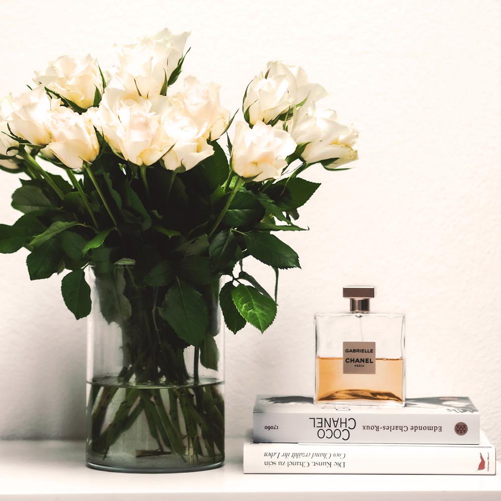 tavolo con libri, bottiglia profumo e fiori